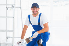 Handyman with paintbrush and can at home stock image
