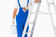 Handyman with paintbrush and can on ladder Royalty Free Stock Photography