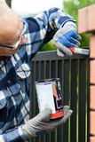 Handyman painting metal fence Royalty Free Stock Photo
