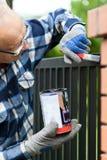 Handyman painting metal fence Royalty Free Stock Photo