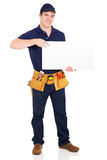 Handyman pointing white board. Happy young handyman pointing at blank white board over white background Royalty Free Stock Image
