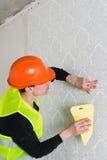 Handyman putting up wallpaper Stock Images