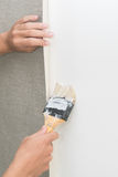 Handyman putting up wallpaper on the white wall Stock Images