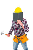 Handyman reading diary and holding hammer Stock Photography
