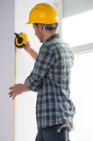 Handyman. Rear view of confident craftsperson in hardhat measuring the wall level stock photo