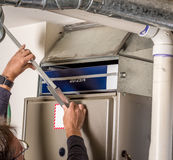 Handyman removes furnace pannel cover. Furnace pannel removed to replace filter stock images