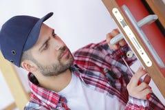 Handyman repair door lock in room. Handyman repair the door lock in the room Royalty Free Stock Photos