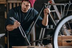 Handyman repairing bike at basement royalty free stock image