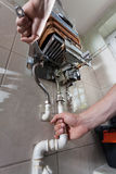 Handyman repairing gas water heater Stock Photo