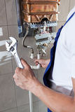 Handyman repairing gas water heater. Repairman fixing a gas water heater with a wrench royalty free stock photography