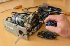 Handyman repairing jigsaw - close-up royalty free stock photo