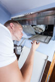 Handyman repairing kitchen extractor fan Royalty Free Stock Image