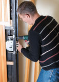 Handyman repairing lock. With drill stock images