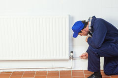 Handyman repairing a radiator Stock Image