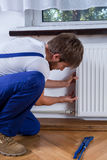Handyman repairing radiator Stock Photos