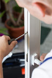 Handyman repairing window with screwdriver Royalty Free Stock Photos