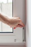 Handyman repairs plastic window with a hexagon. Workman adjusts the operation of the plastic window.  Stock Photography