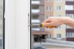 Handyman repairs plastic window with screwdriver. Workman adjusts the operation of the plastic window.  Stock Photos