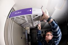 Handyman replaces the filter in the hot air furnace at a home. Thick furnace filter demonstration by a handyman stock images