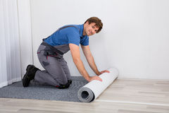 Handyman Rolling Carpet On Floor Stock Photos