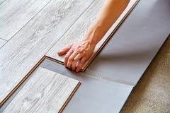 Handyman`s Hands Laying Down Laminate Flooring Boards Royalty Free Stock Image