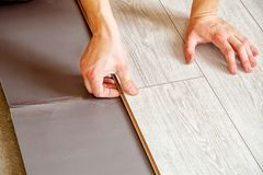 Handyman`s hands laying down laminate flooring boards. Handyman laying down laminate flooring boards while renovating a house. hands closeup Stock Images
