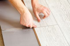 Handyman`s hands laying down laminate flooring boards. Handyman laying down laminate flooring boards while renovating a house. hands closeup Royalty Free Stock Photography