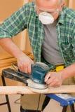 Handyman sanding wooden board diy home renovation. Handyman mature professional sanding wooden board diy new home renovation Royalty Free Stock Photos