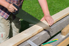 Handyman sawing. Long wooden plank outdoors Royalty Free Stock Photos