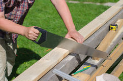 Handyman sawing. Long wooden plank outdoors Stock Photos