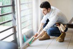Handyman sealing a window frame. Young handyman wearing a tool belt and using a sealing gun to seal a glass door frame on a house stock image
