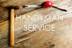 Handyman service written on wooden background with hammer and measuring tape stock image