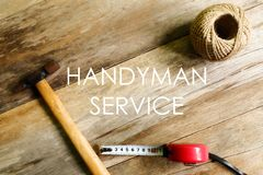 Handyman service written on wooden background with rope,measuring tape and hammer royalty free stock photo
