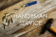Handyman service written on wooden background with screwdriver and hammer stock photography