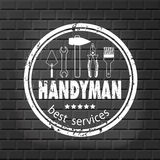 Handyman services  design for your logo or emblem with stamp on the gray brick wall. Set of workers tools. Stock Image