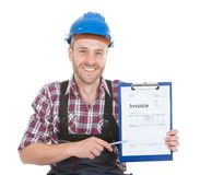Handyman showing invoice on clipboard. Portrait of smiling handyman showing invoice on clipboard over white background Stock Image