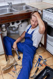 Handyman sitting on the kitchen floor Stock Images