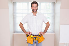 Handyman smiling at camera in tool belt Royalty Free Stock Image