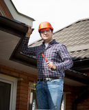 Handyman standing on high ladder and inspecting house roof Royalty Free Stock Photos