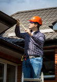Handyman standing on high ladder and measuring roof with tape. Young handyman standing on high ladder and measuring roof with tape Stock Photography