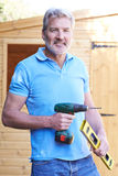 Handyman Standing Outside Garden Shed With Tools Royalty Free Stock Images