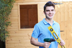 Handyman Standing Outside Garden Shed With Tools Stock Photography