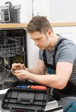 Handyman with tablet pc. Repairing domestic dishwasher in the kitchen stock photo