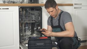 Handyman with tablet pc repairing domestic dishwasher