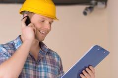 Handyman talking at phone. Cheerful craftsperson talking at mobile phone and looking at clipboard royalty free stock images