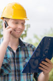 Handyman talking at phone. Stock Image