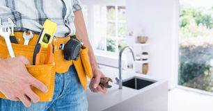 Handyman with tool belt at home Stock Photo