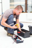 Handyman with Tool Box. Handyman searching in his tool box for the necessary tools stock image