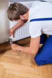 Handyman trying to fix heater Royalty Free Stock Photo