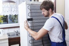 Handyman trying to move a fridge. At house Royalty Free Stock Image
